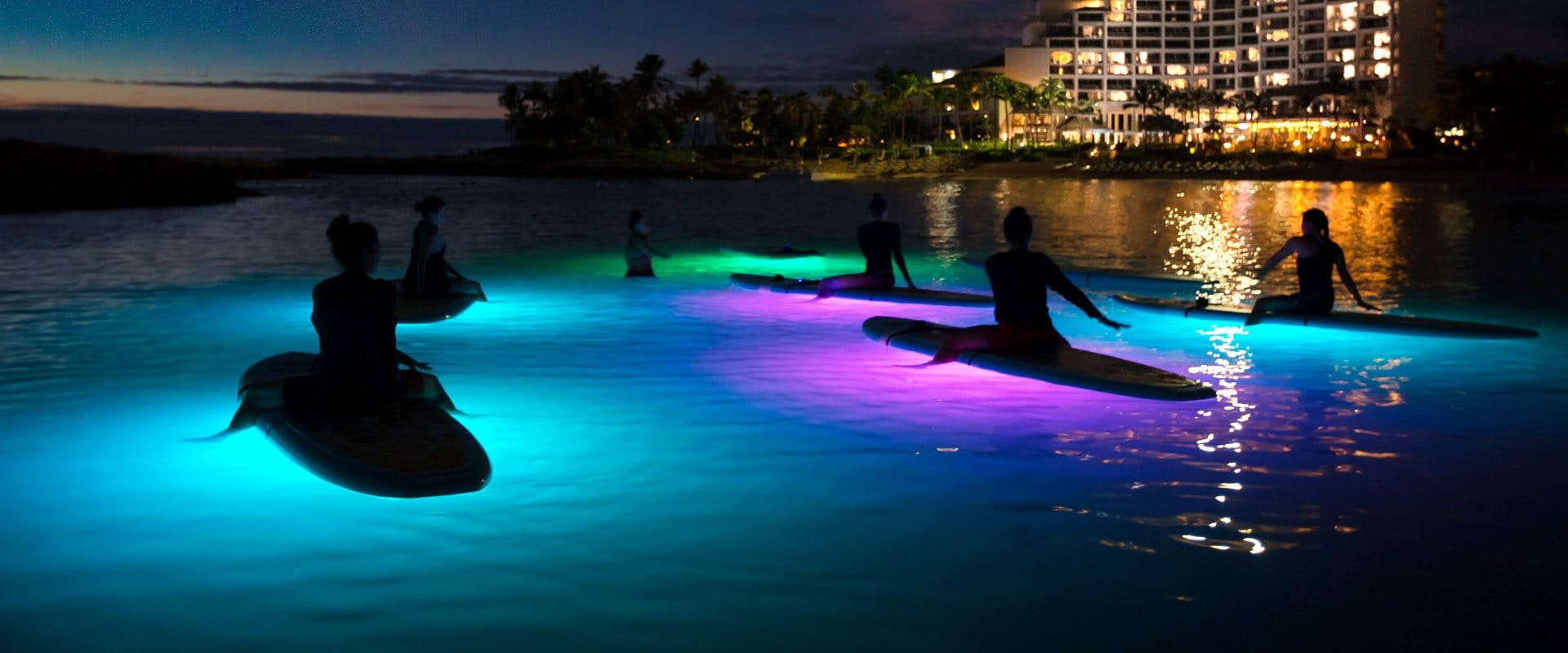 Nighttime yoga on a glowing stand up paddle board